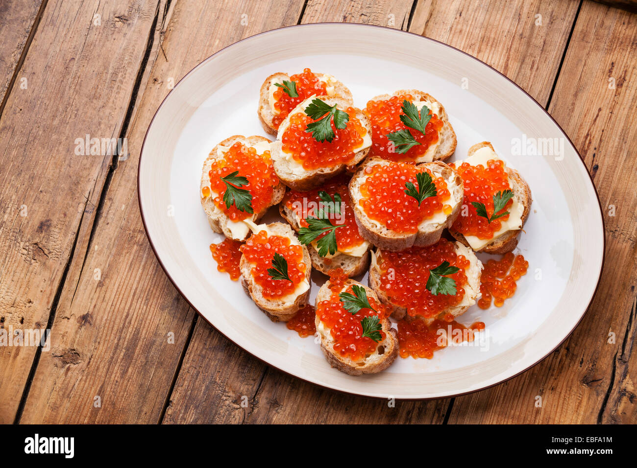 Sandwiches with Salmon red caviar and parsley on white plate on wooden background - Stock Image
