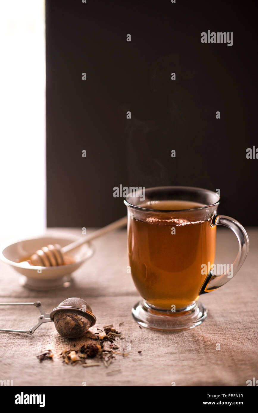 Steaming cup of hot tea with loose leaf tea in foreground and honey with dipper in background. Rustic, linen surface. - Stock Image