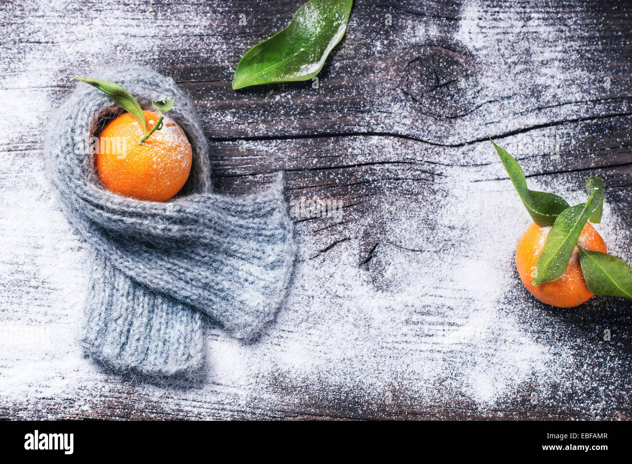 Tangerine in scarf over wooden background with snow and leaf. Top view. - Stock Image