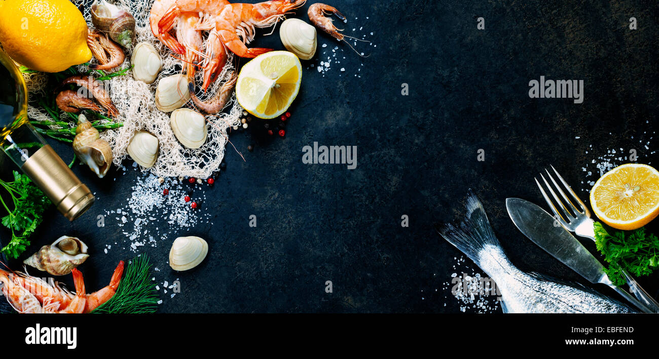 Delicious fresh fish and seafood on dark vintage background. Fish, cockles and shrimps with aromatic herbs, spices - Stock Image