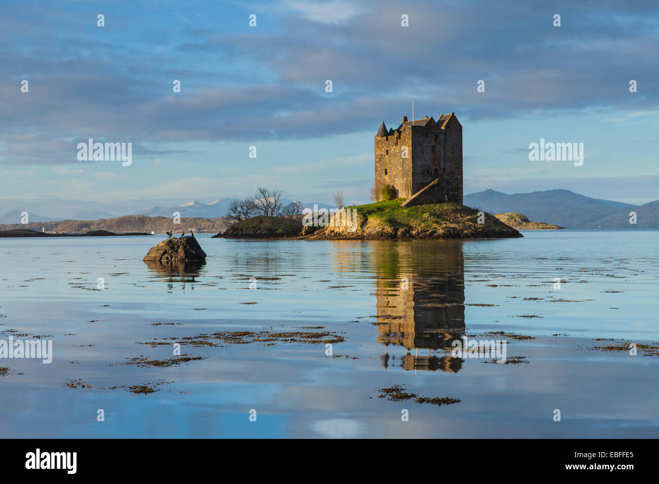 Castle Stalker at sunrise in winter. A castle surrounded by water on the west coast of Scotland - Stock Image