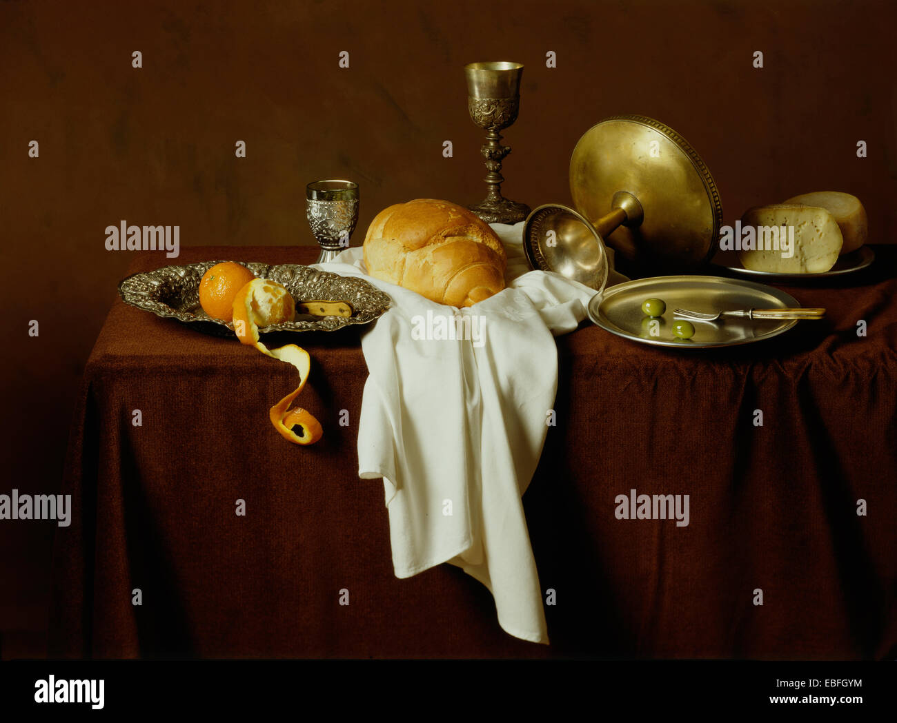 Still life, old style image of bread, cheese, olives, oranges on a brown table and brown background Stock Photo