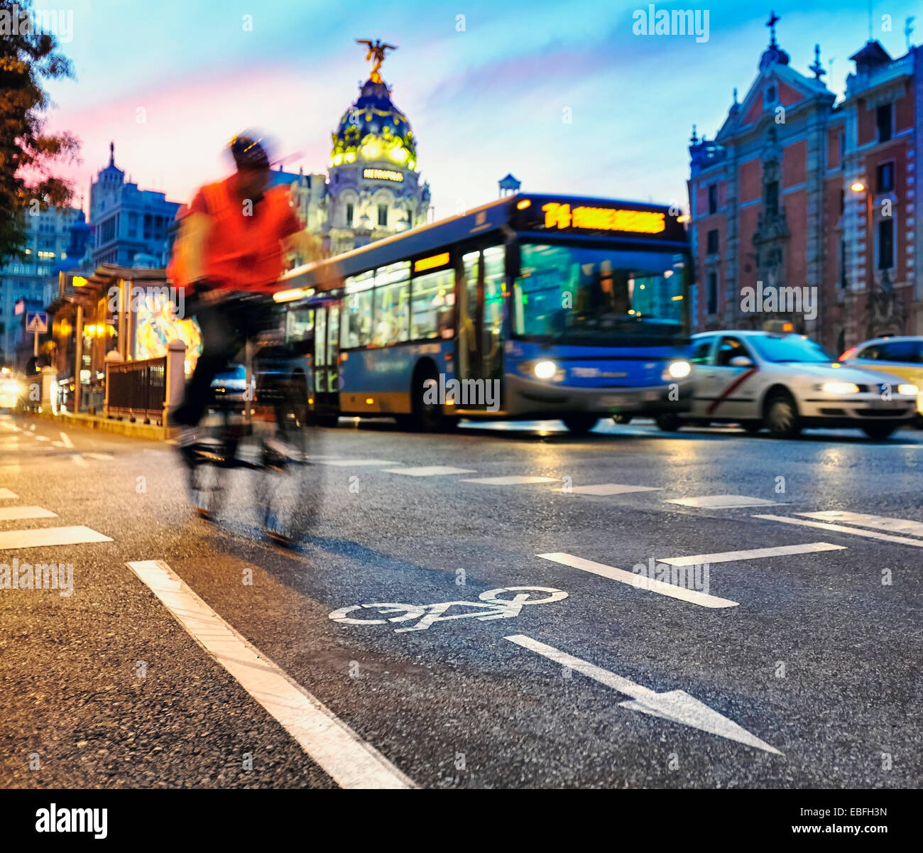 Cyclist at the cycle lane of Alcal‡ street with the Metropolis building at the background. Madrid, Spain. Stock Photo