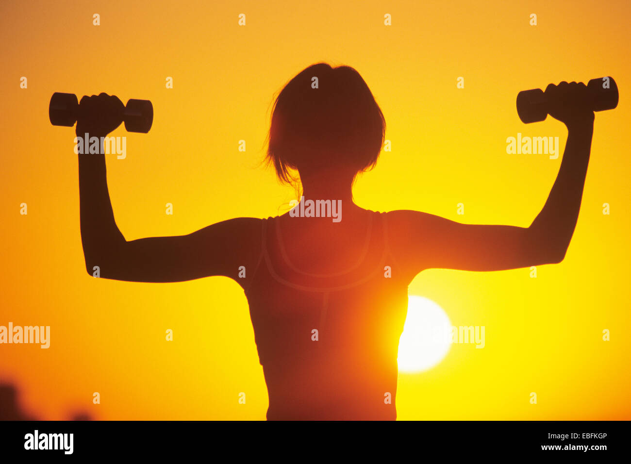 Silhouette of Woman with Dumbbells - Stock Image