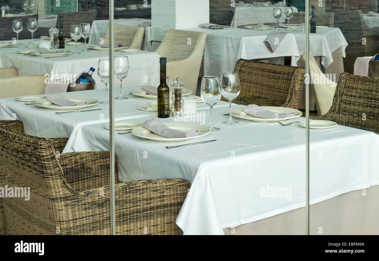 TABLE SET FOR LUNCH OR DINNER WITH PLATES WINE GLASSES TABLECLOTH AND NAPKINS - Stock Image