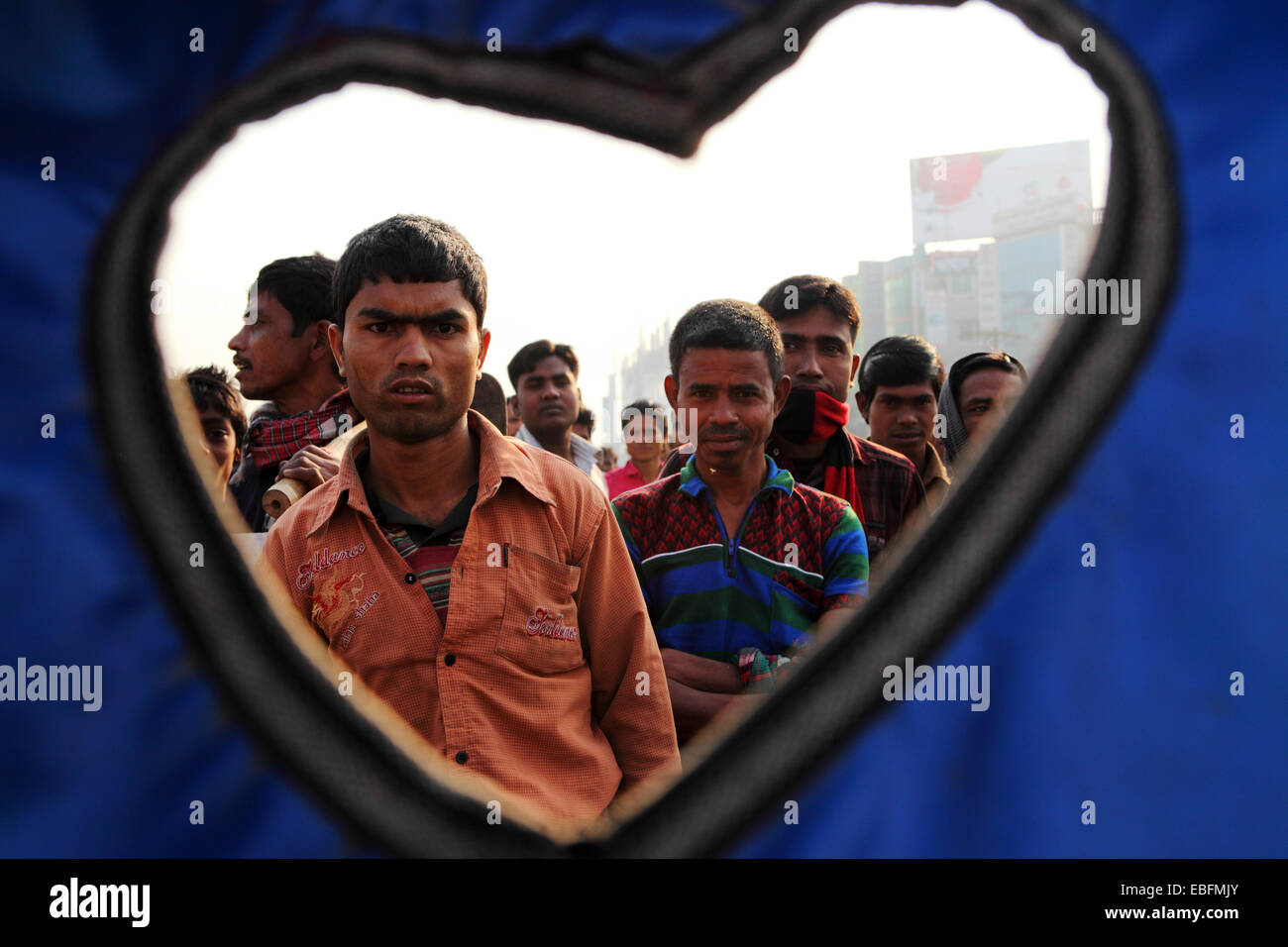 People on a street in Dhaka, Bangladesh. They are seen through the heart shape of a rickshaw canopy. - Stock Image