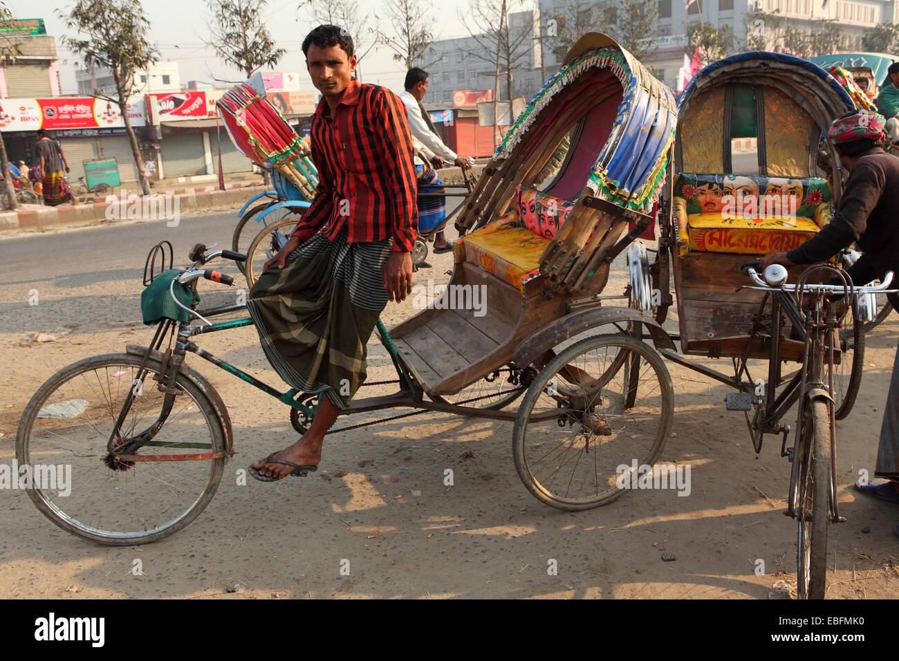 A rickshaw driver in Dhaka, Bangladesh. The city has around 400,000 rickshaws. - Stock Image