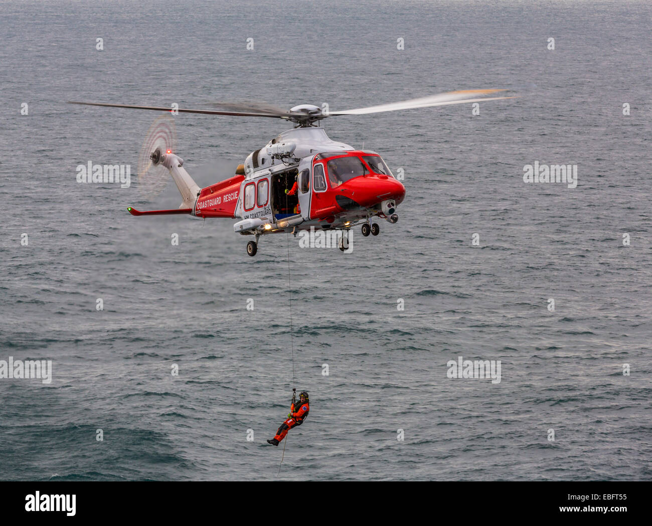 A view of an Augusta HM Coastguard Search and Rescue helicopter with the winchman lowered to the sea - Stock Image