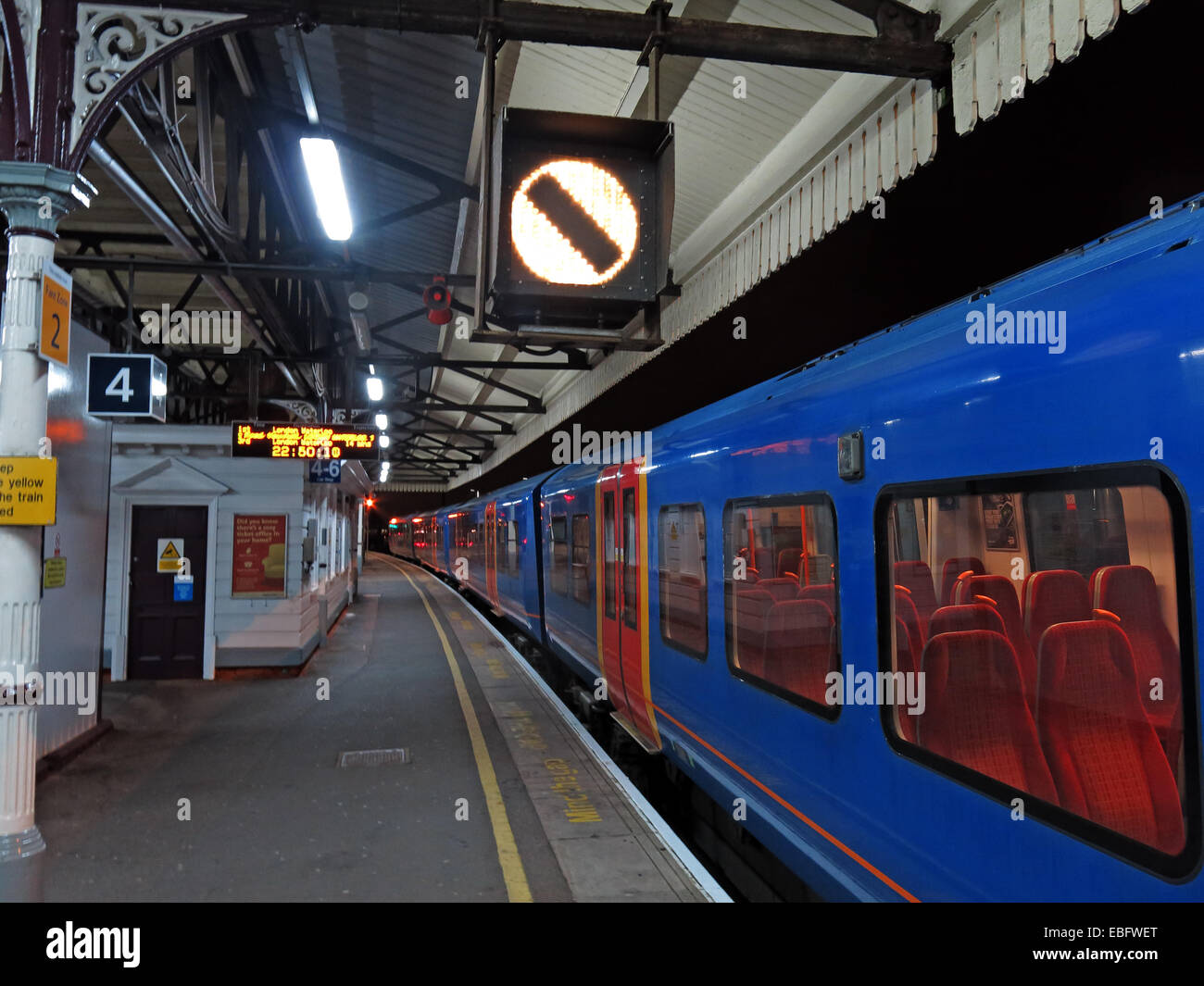 SW Trains EMU at Clapham Junction Railway Station at night, on platform 4 - Stock Image