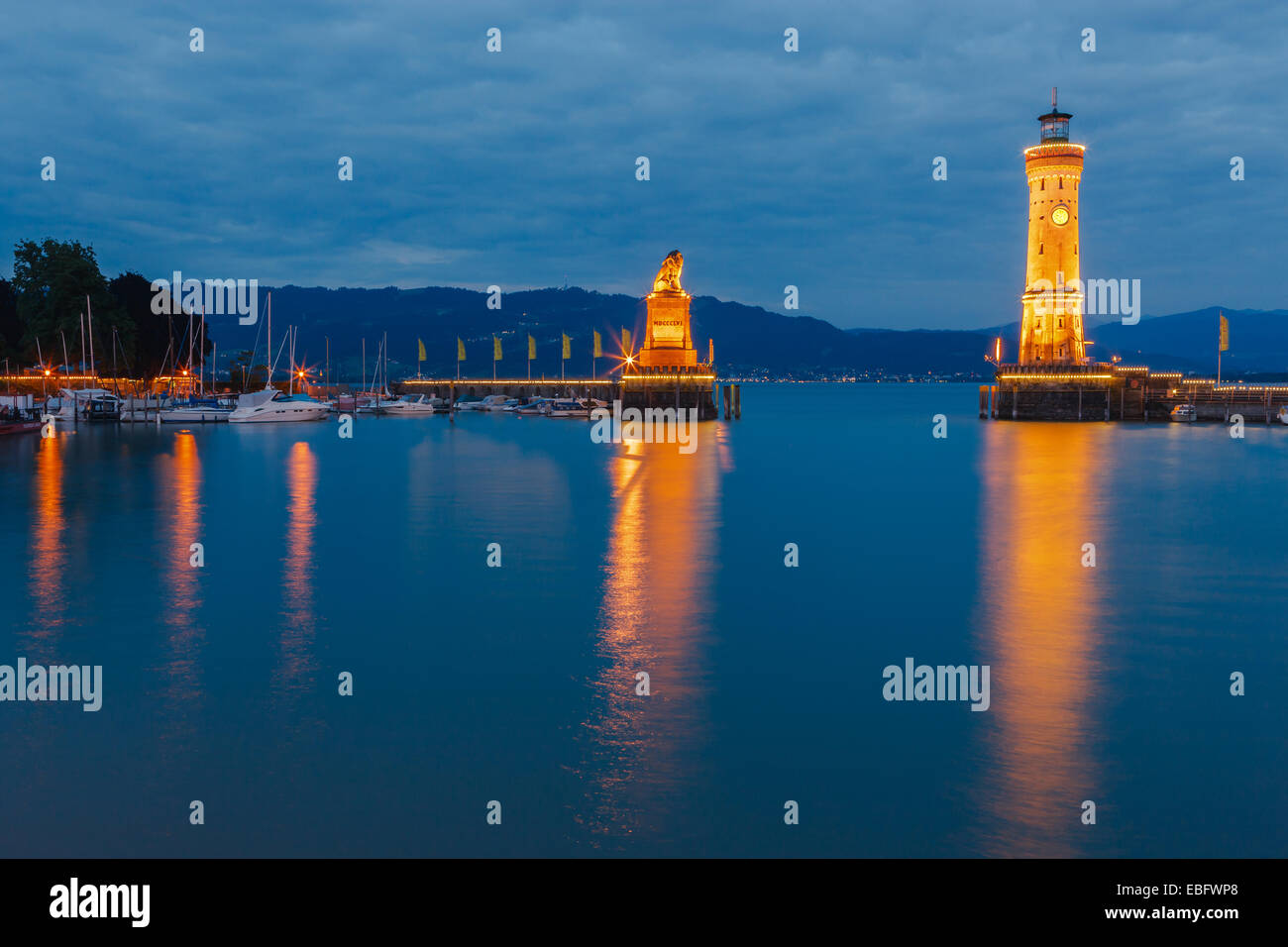 View of harbor entrance and lighthouse at night in Lindau at lake Constance, Bavaria, Germany Stock Photo