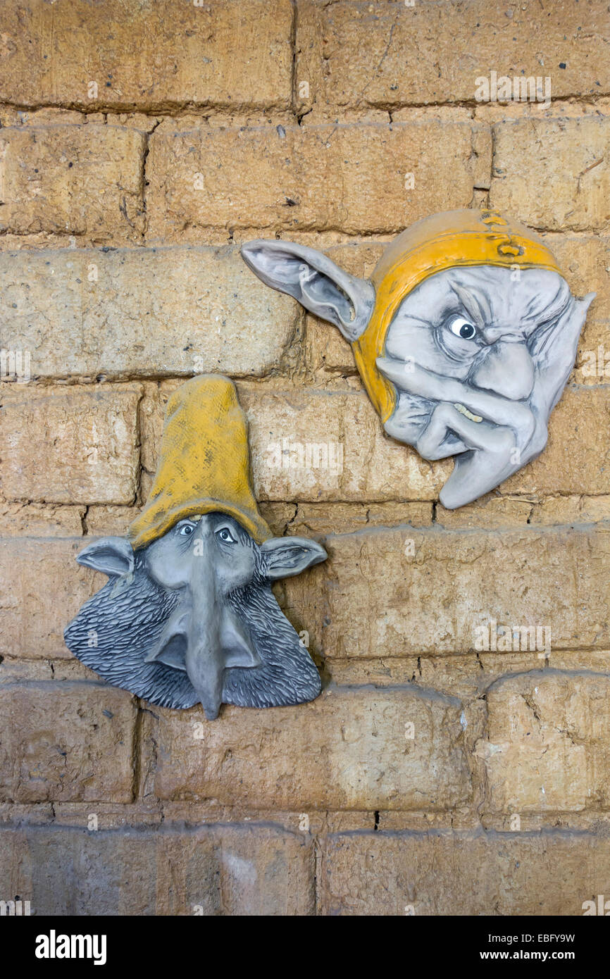 Two plaques of ugly faces on a mud brick wall - Stock Image
