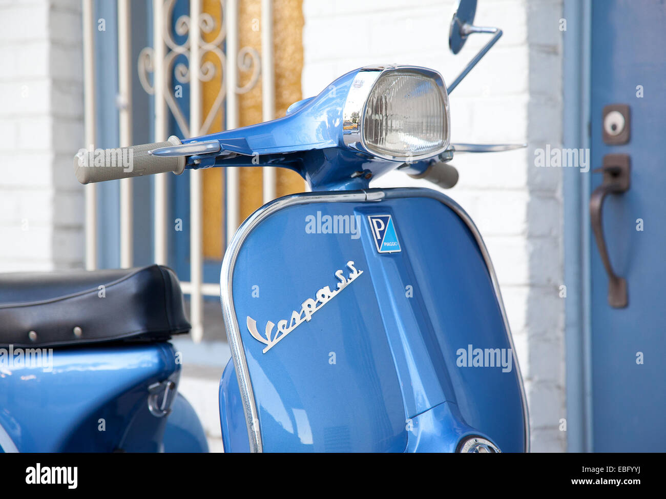 Detail of light blue super sport Vespa scooter in front of a building - Stock Image
