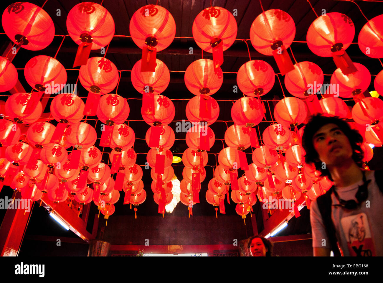 Man standing below red lanterns at Jin De Yuan temple, Jakarta, during the celebration of Chinese New Year. - Stock Image