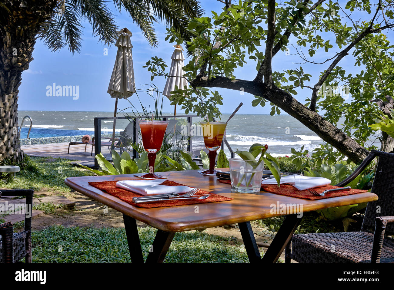 Outdoor dining table set for two in a tropical setting with ocean view thailand s e asia