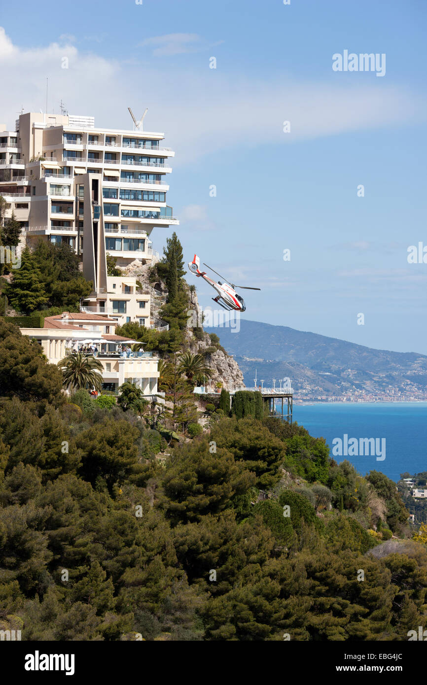 HELICOPTER (eurocopter ec130) TAKING OFF FROM A CLIFFTOP FIVE-STAR HOTEL. Vista Hotel, Roquebrune-Cap-Martin, Alpes - Stock Image