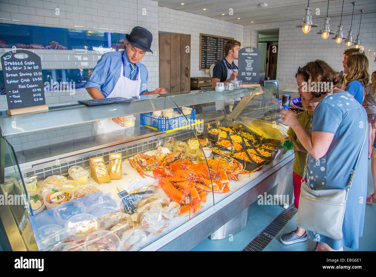 An Interior view of staff serving customers at Stein's Fisheries fresh fish counter Padstow Cornwall England - Stock Image