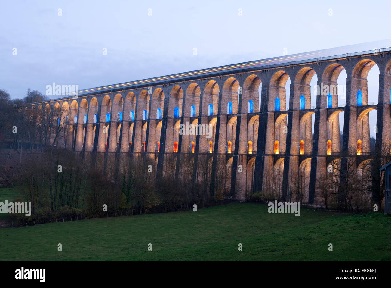 3-SECOND TIME EXPOSURE OF A TRAIN ON A VIADUCT. LED lights illuminate the 2nd & 3r floor. Chaumont, Haute-Marne, - Stock Image
