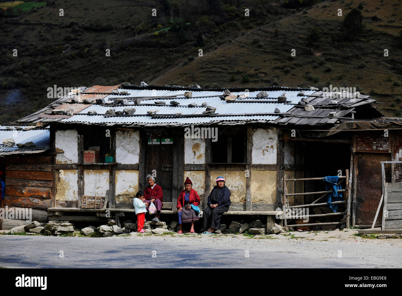 Small shop on the roadside with people sitting out the front, Pela La Pass, Wangdue Phodrang District, Bhutan - Stock Image