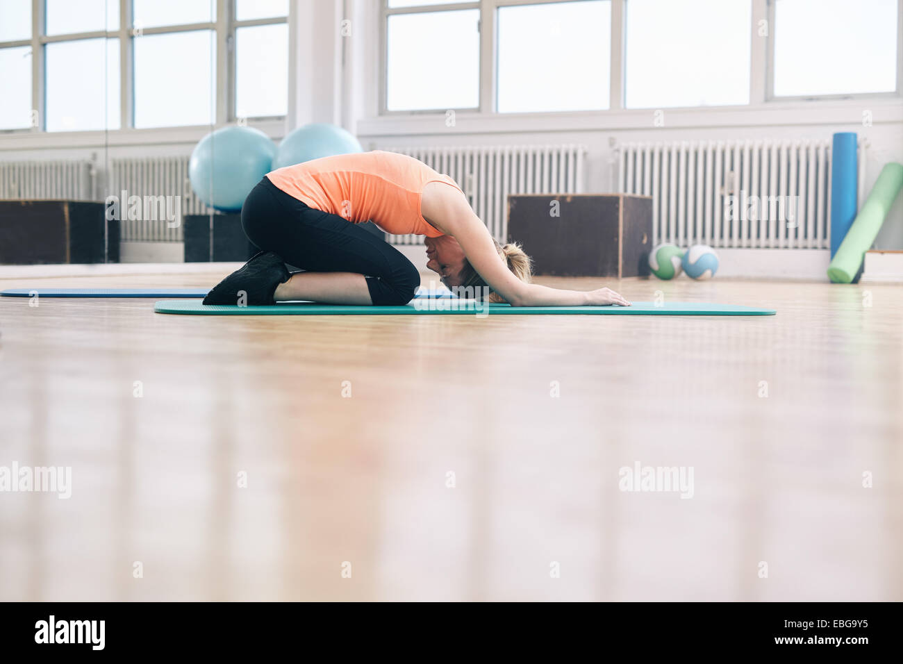 Portrait of woman doing a forward bend yoga exercise. Fitness woman practicing yoga at gym. Balasana - Child pose. - Stock Image