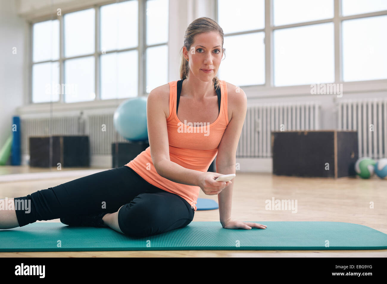 Fitness woman sitting on exercise mat holding her smartphone. Caucasian woman using mobile phone while at gym. - Stock Image