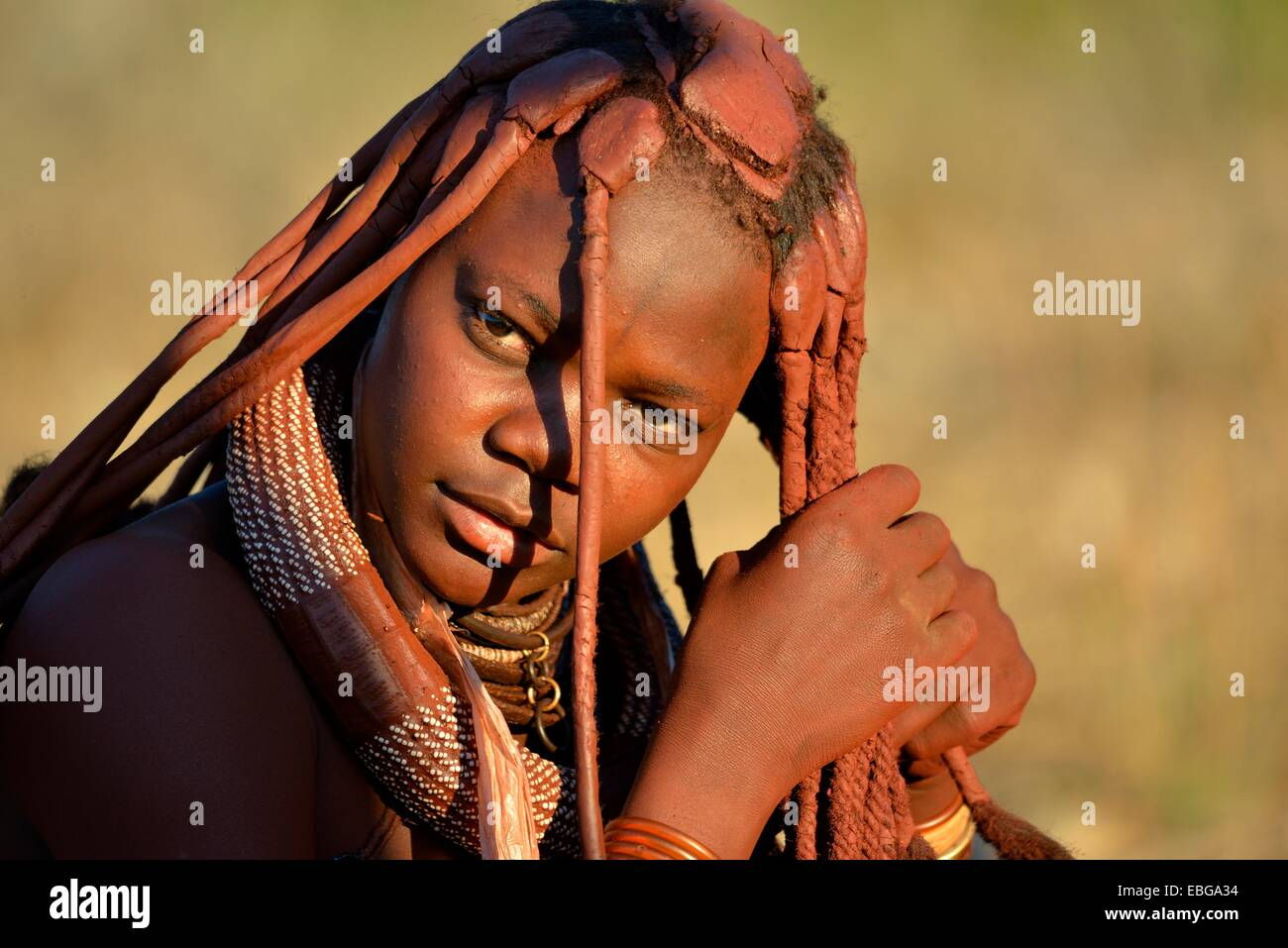 Young Himba woman doing her hair, Ombombo, Kaokoland, Kunene, Namibia - Stock Image