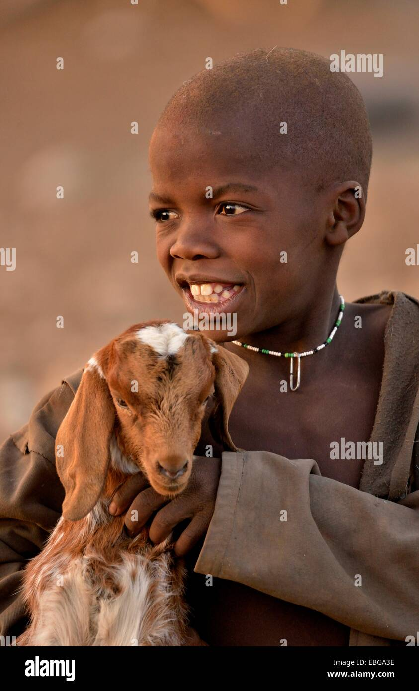 Himba boy with a goat, Ombombo, Kaokoland, Kunene, Namibia Stock Photo