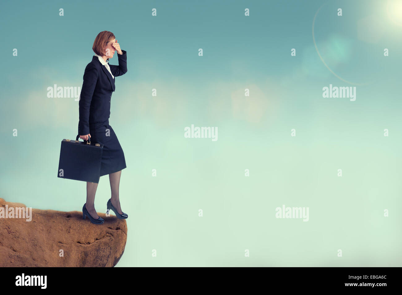 businesswoman on the edge of a cliff look before you leap business concept - Stock Image