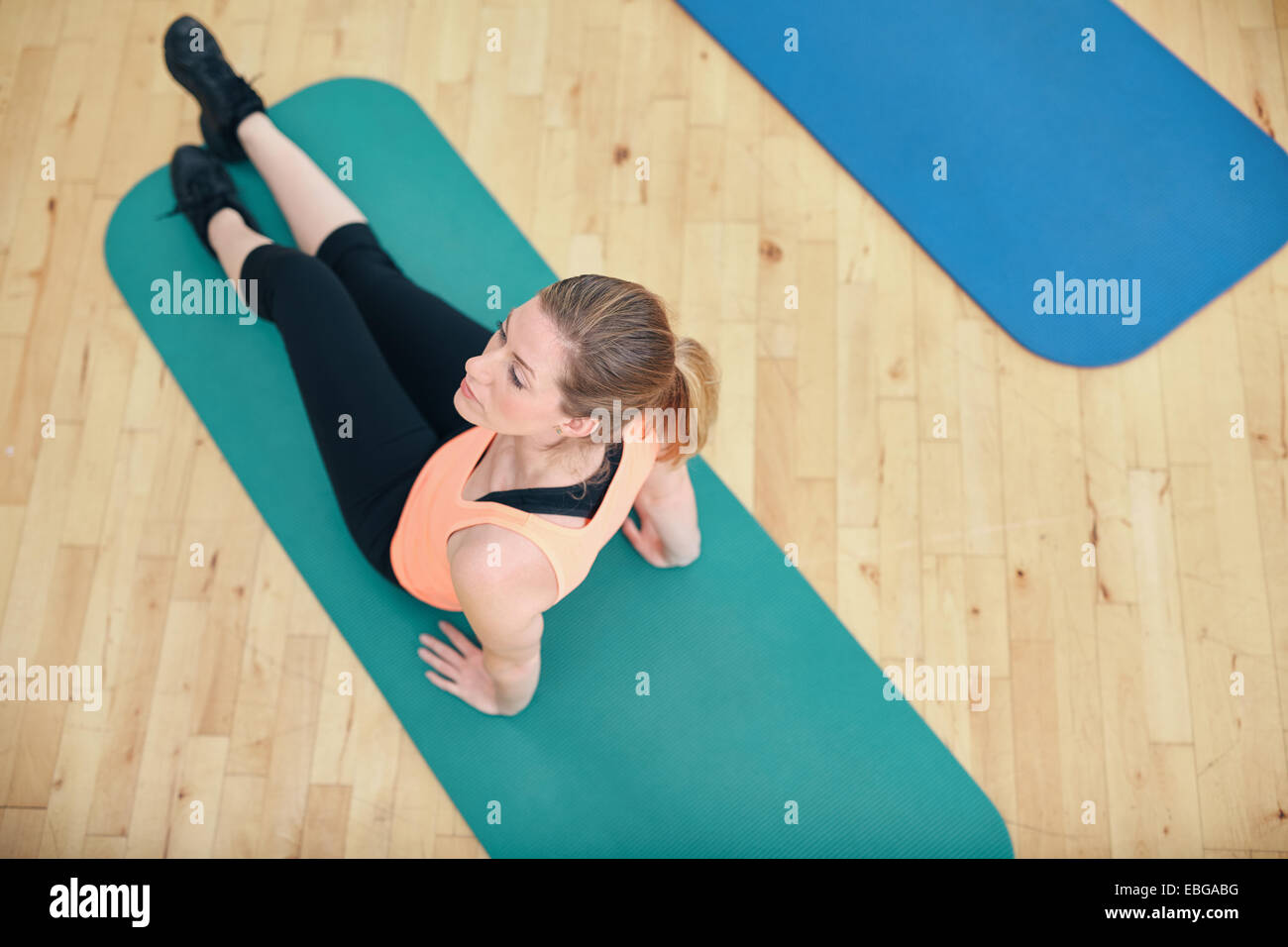 Top view of fitness woman exercising on a fitness mat . Fit woman working out at gym. - Stock Image
