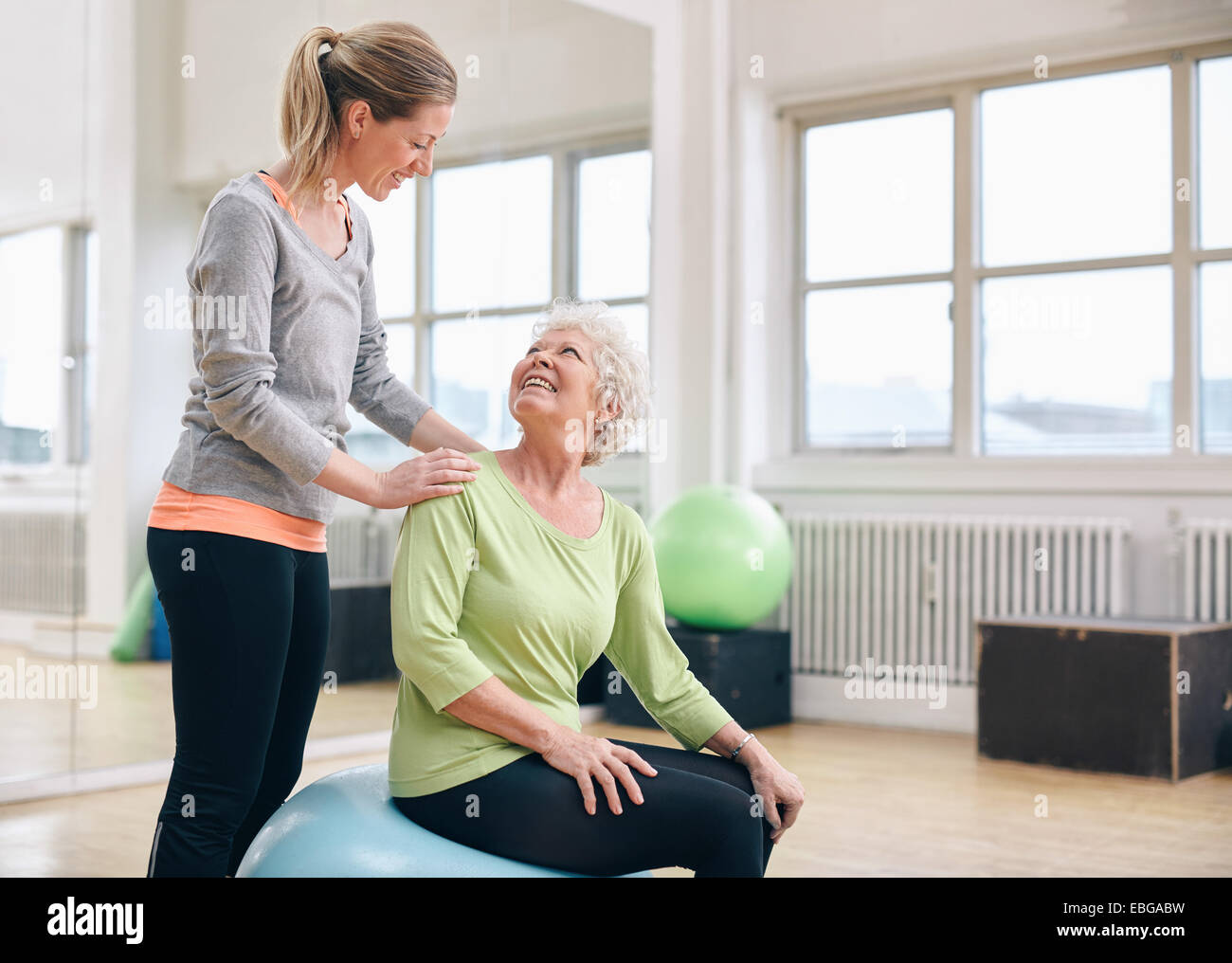 Female instructor assisting senior woman exercising in health club. Older woman assisted by personal trainer at - Stock Image