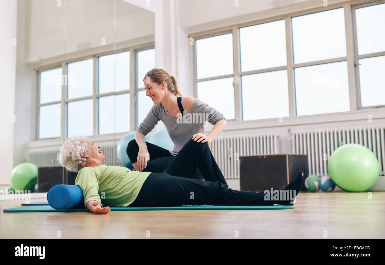 Senior woman having a friendly chat with her personal trainer while exercising at gym. Elder woman doing pilates - Stock Image