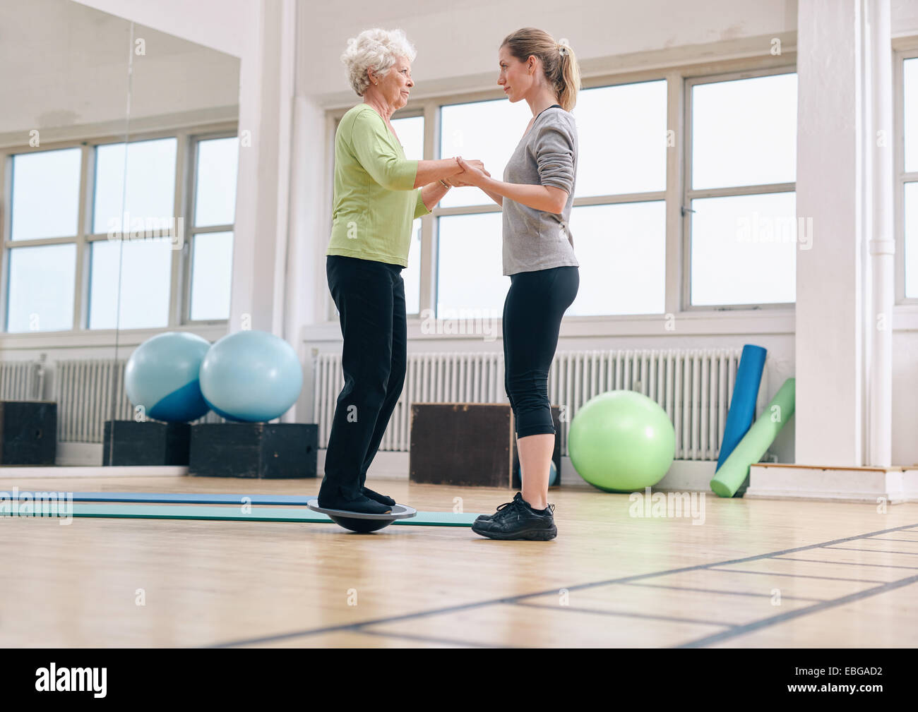 Female trainer helping senior woman standing on a balance board at gym. Elder woman exercising being assisted by - Stock Image