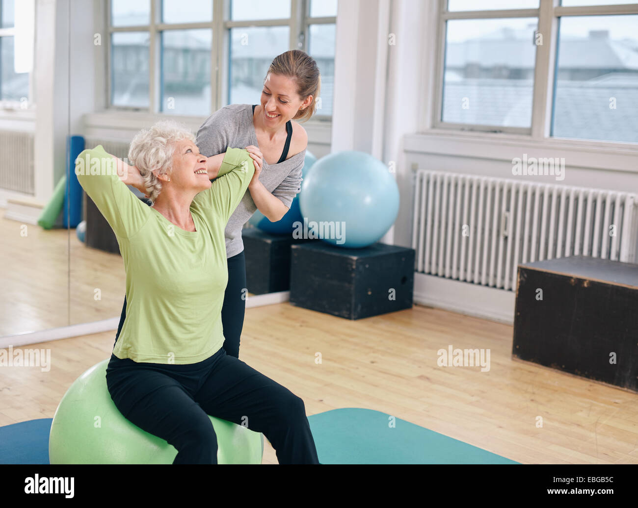 Mature woman working out on a fitness ball with help from personal trainer at gym. Happy senior woman exercising - Stock Image