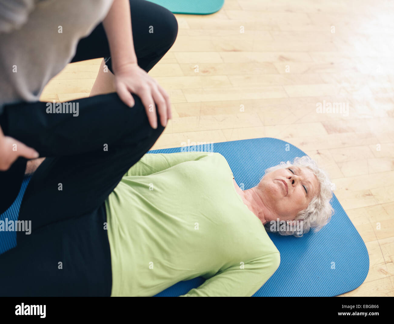 Senior woman lying on exercise mat with her personal trainer helping her doing leg stretches at gym. Elder woman - Stock Image