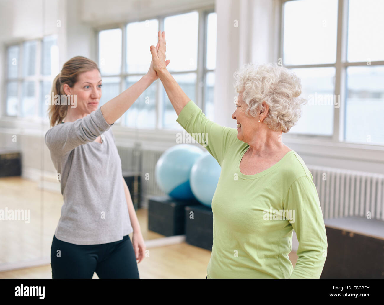 Senior woman giving high five to her personal trainer at gym. Excited old woman rejoicing health success with her - Stock Image