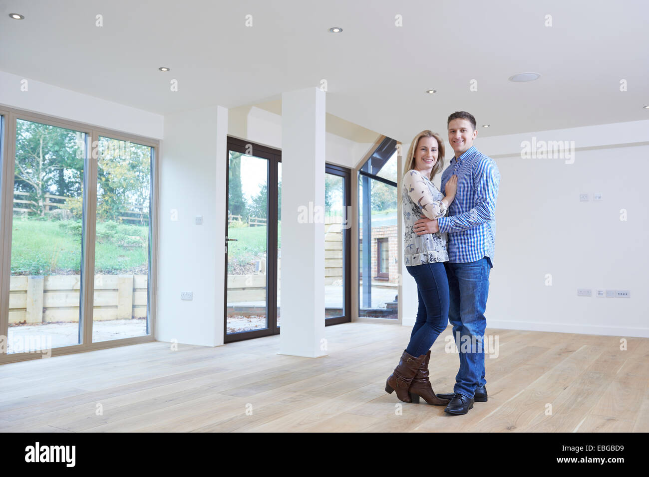Portrait Of Happy Young Couple In New Home - Stock Image