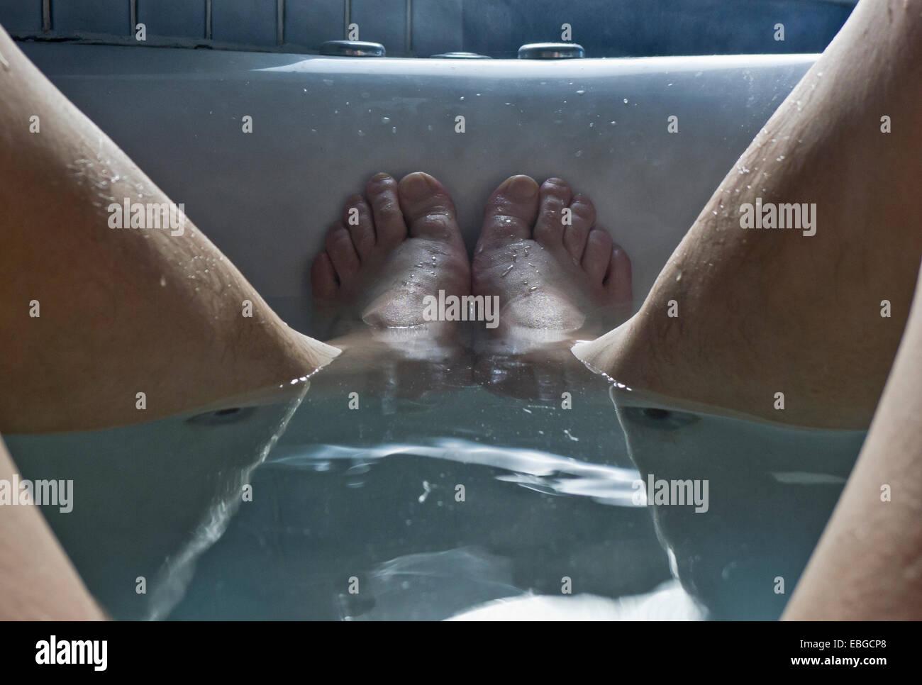 A man's feet in the bathtub. - Stock Image