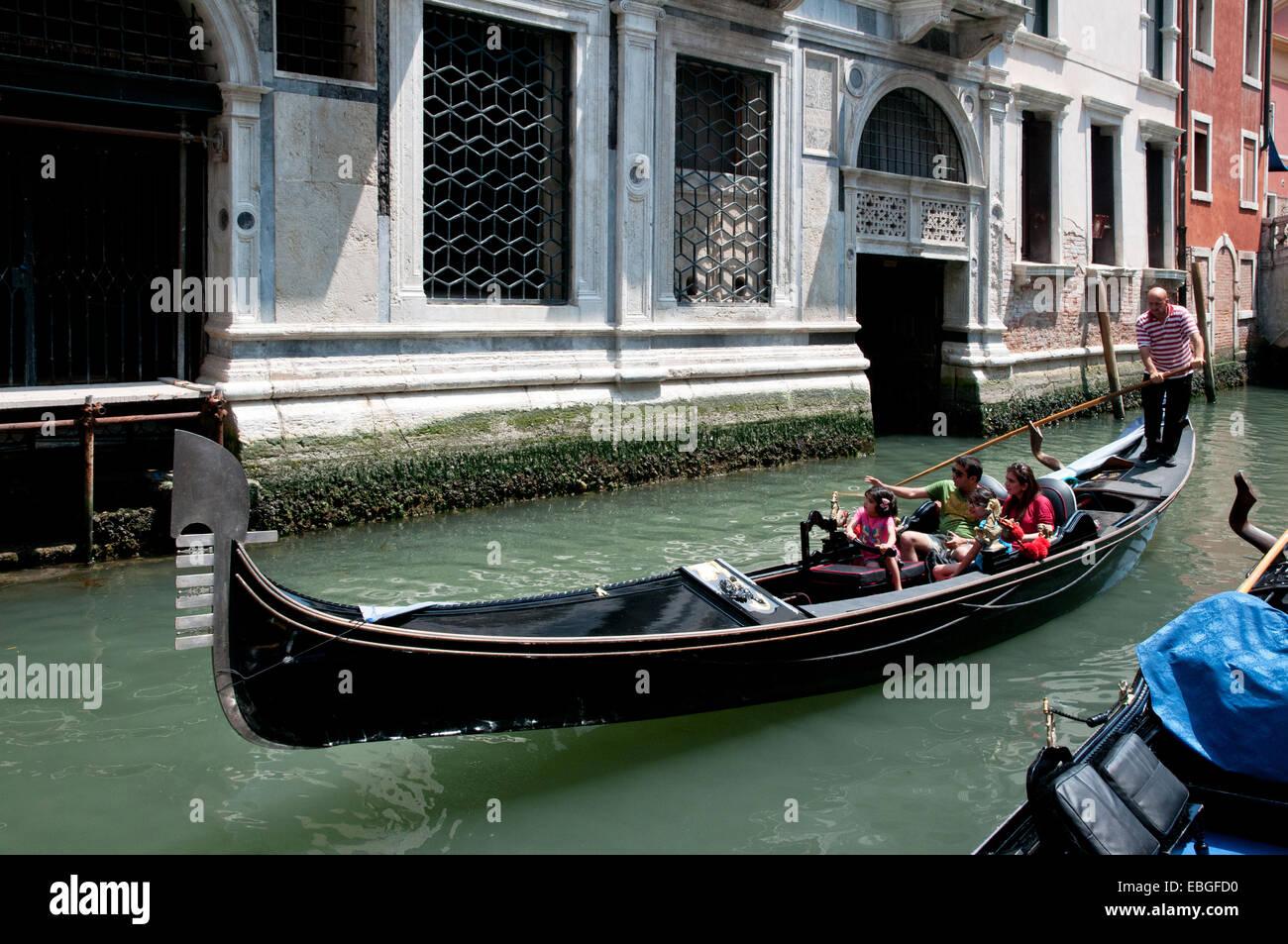 Family enjoying a gondola ride on canal Rio de la Canonica Venice Italy GONDALA FAMILY CANAL VENICE ITALY - Stock Image