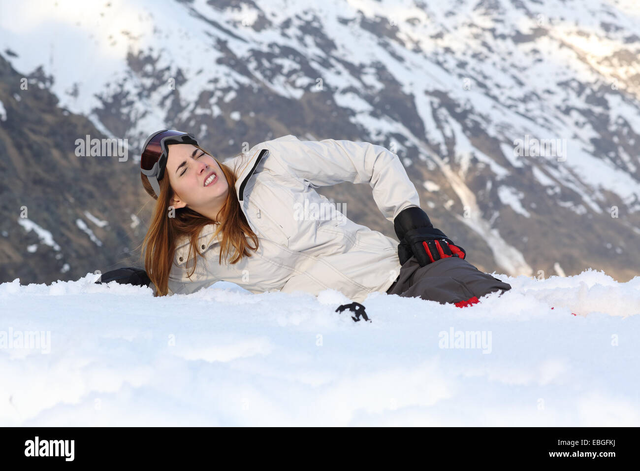 Skier woman hurt lying in the snow of a high mountain - Stock Image