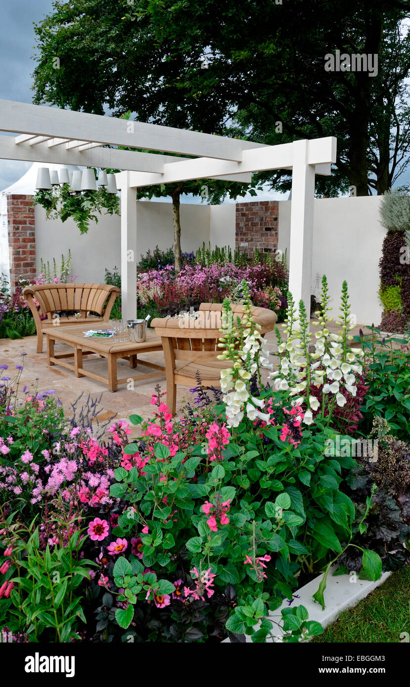 A contemporary garden with terraced area and stylish wooden furniture surrounded by colourful flowering borders Stock Photo