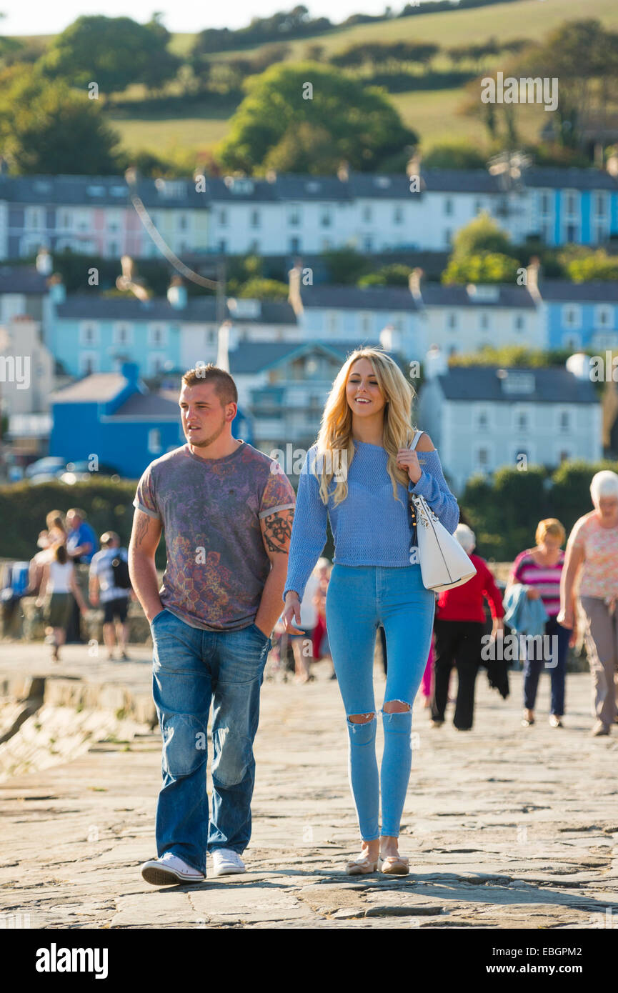 September sunshine: A happy smiling young couple walking Cei Newydd / New Quay, on the Cardigan Bay coast of Ceredigion - Stock Image
