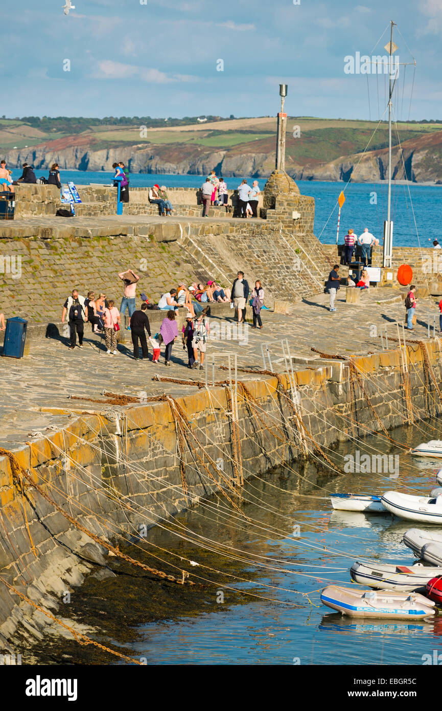 September sunshine: People relaxing on the quayside at Cei Newydd / New Quay, on the Cardigan Bay coast of Ceredigion, - Stock Image