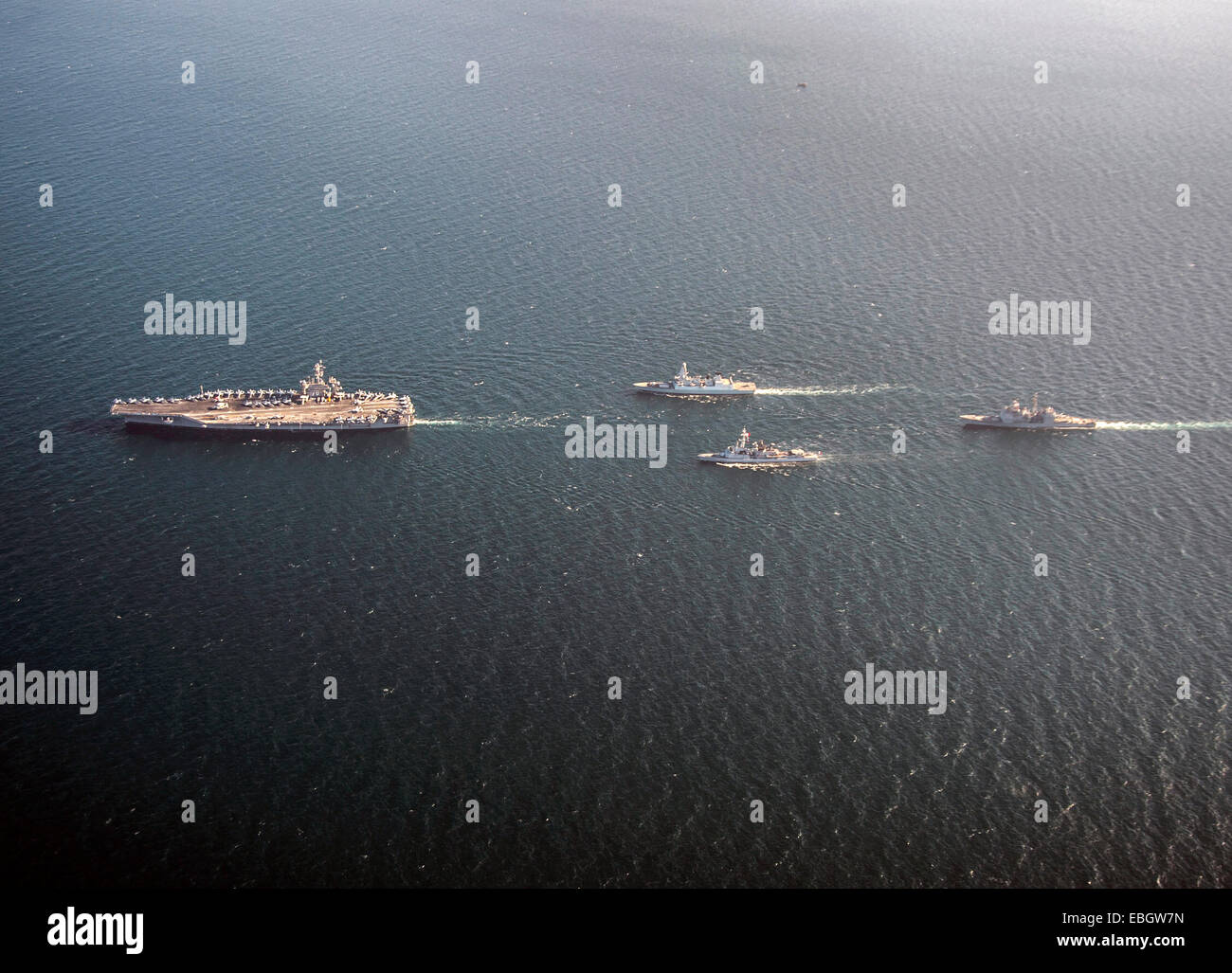 US Navy nuclear aircraft carrier USS Carl Vinson sails in formation with the Royal Navy Daring-class air defence - Stock Image