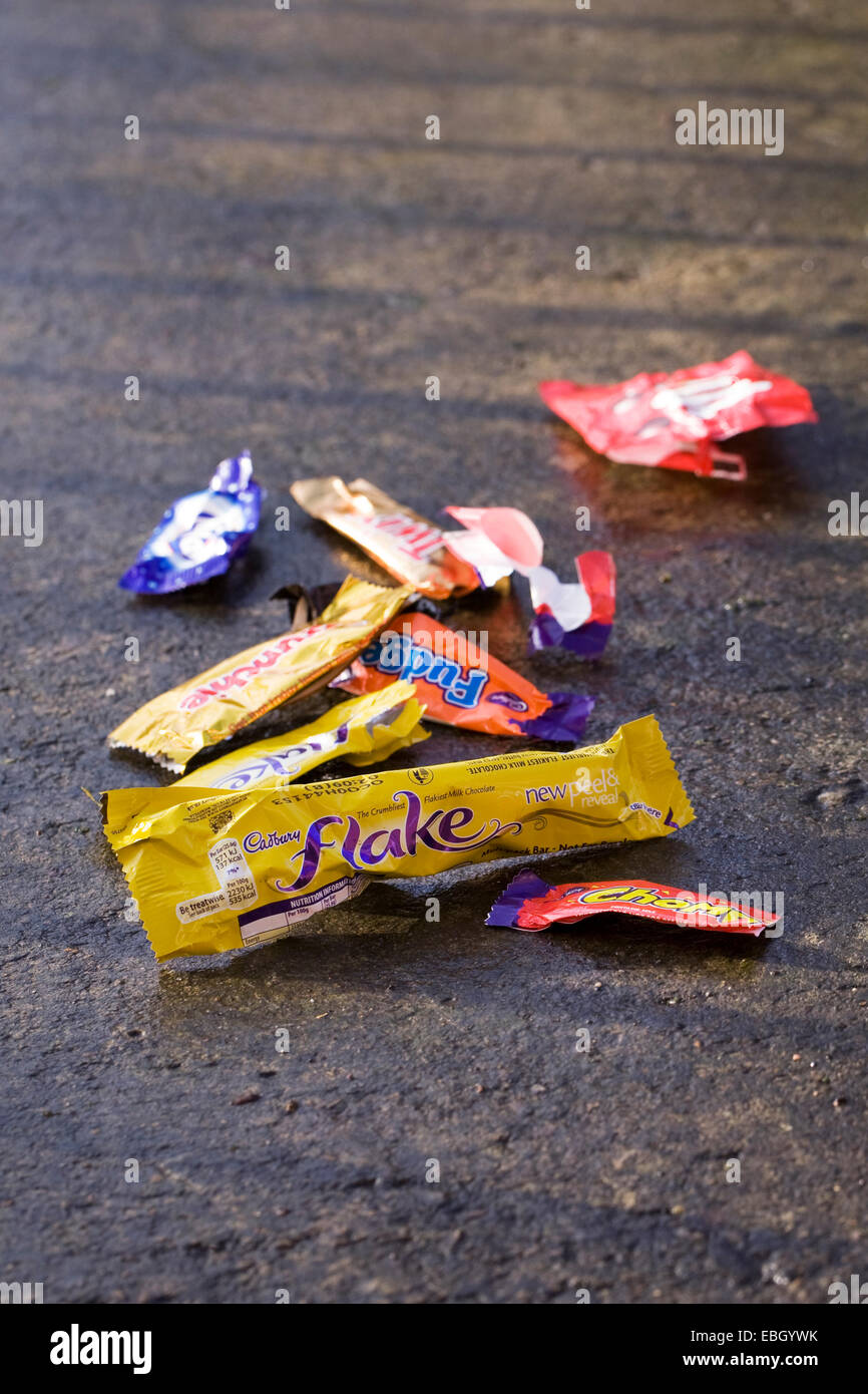 Empty sweet wrappers littering the pathway. - Stock Image