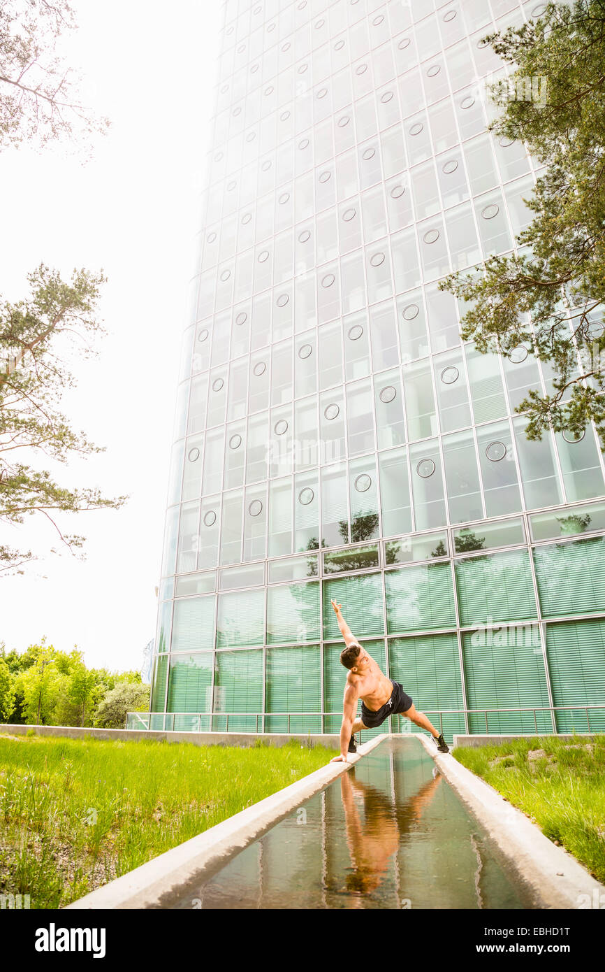 Personal trainer doing outdoor training in urban place, Munich, Bavaria, Germany - Stock Image