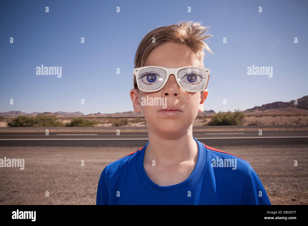 Portrait of boy on roadside wearing spectacles with staring eyes - Stock Image