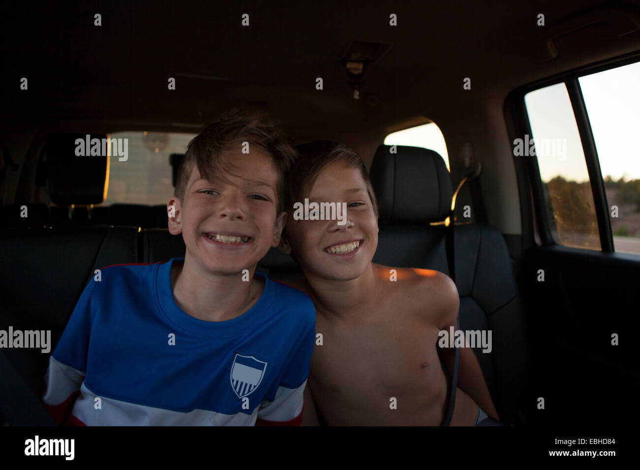 Portrait of brothers smiling in car back seat - Stock Image