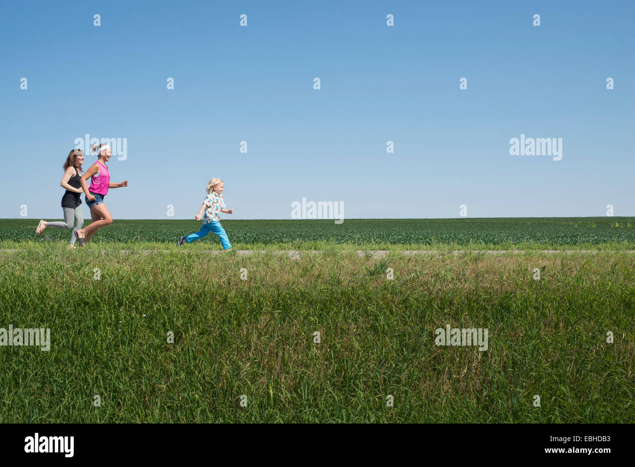 Three people running through field - Stock Image