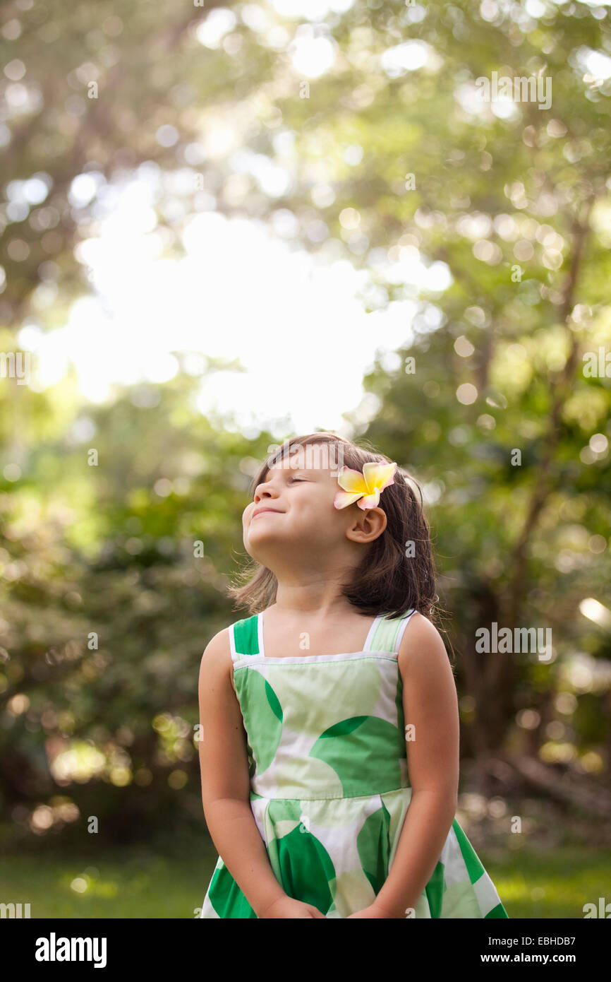 Young girl in garden, wearing flower in her hair - Stock Image