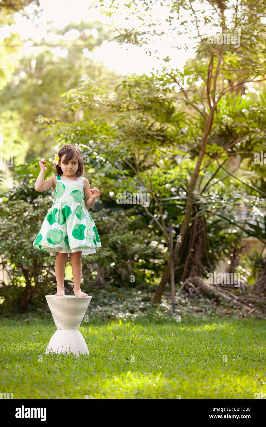 Young girl in garden, standing on pedestal - Stock Image