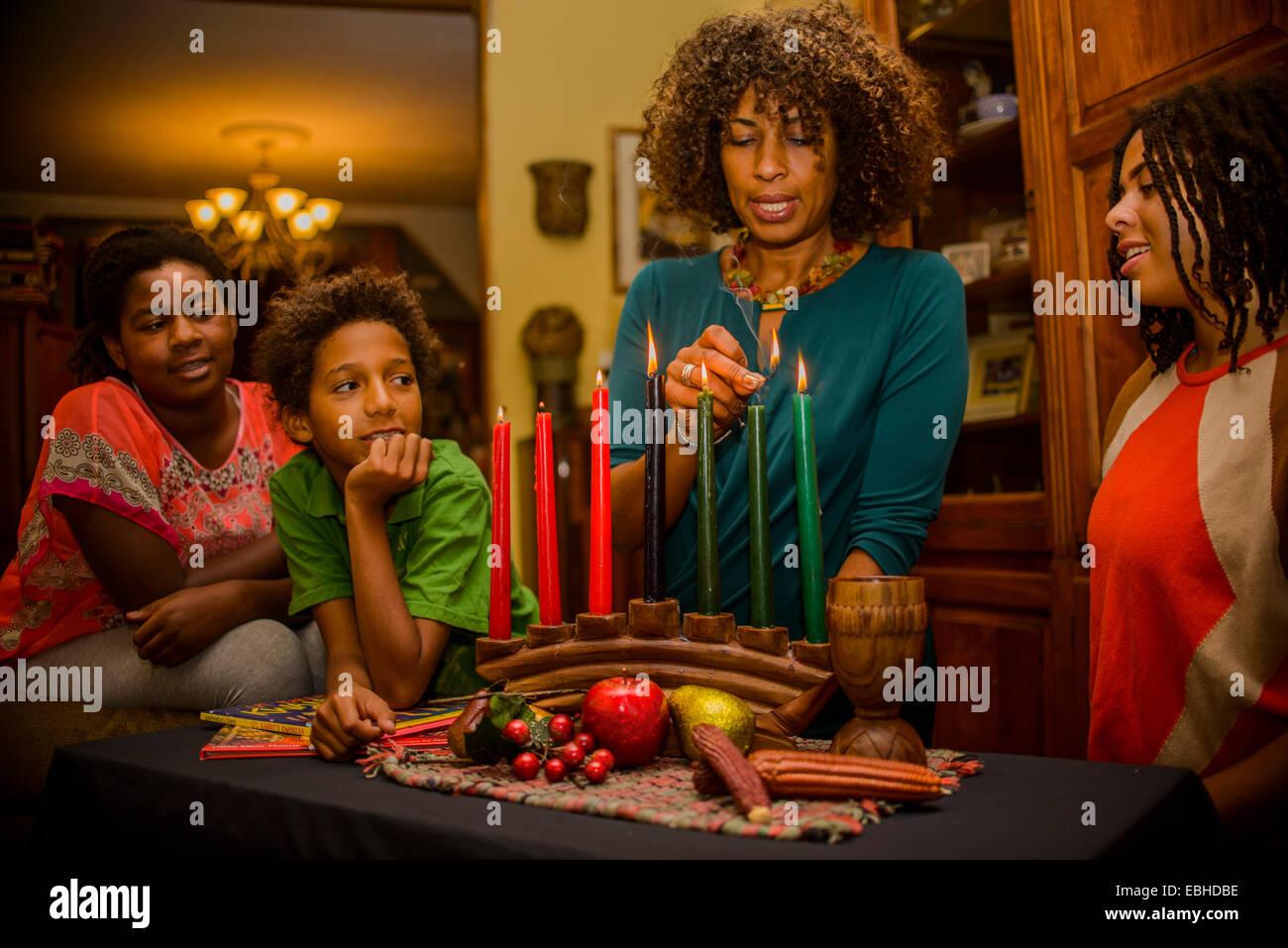 Family lighting kinara candles, celebrating Kwanzaa - Stock Image
